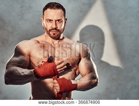 Handsome Adult Sportsman Posing For A Camera While Wrapping His Hands With Red Tapes For Boxing, Loo