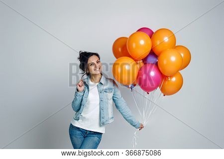 Smiling Girl In Denim Posing With Bright Colorful Air Balloons Isolated On Gray Background. Beautifu