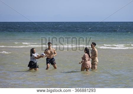 Adelaide, Australia - March 8th, 2020:a Group Of Youngsters Playing Ball In The Shallow Water At Ade