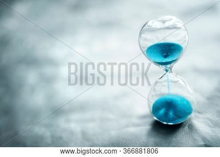 Hourglass on blue background with copy space concept for time