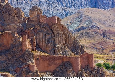 Massive Fortress On The Rocks. The Stone Walls Of The Citadel And The Towers. Castle In The Mountain