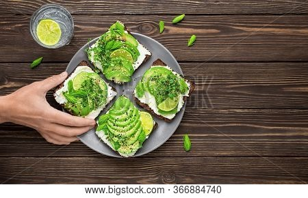 Woman's Hand Takes Sandwich From Plate. Sandwich On Rye Bread With Avocado, Cheese, Micro-greens, Se
