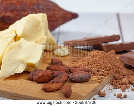 Pieces Of Natural Cocoa Butter, Bar Of Milk Chocolate, Cocoa Powder, Cocoa Pod And Cocoa Beans On Wo