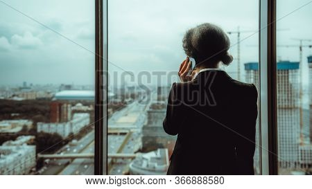 View From Behind Of A Woman Entrepreneur Speaking On The Phone While Standing Next To A Panoramic Wi