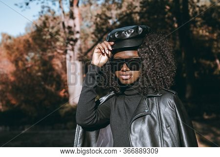 An Outdoor Portrait Of A Dazzling Curly African Female From Guinea In Sunglasses, Leather Cap, And J