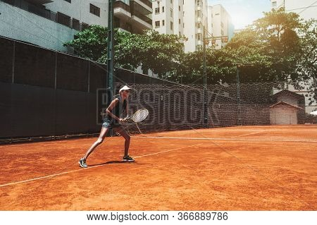 A Young Slim African-american Female Plays Tennis Outdoors In The Training Court; Beautiful Biracial