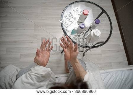 A Sick Person Disinfects His Hands With A Sanitizer