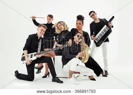 Photo Of Multi Ethnic Music Band In Studio.musicians And Woman Soloist Posing Over White Background
