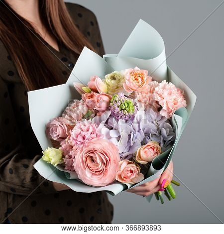 Beautiful Bouquet In The Hands Of A Florist. Of Roses, Carnations, Hydrangeas, Tulips In Brown Paper