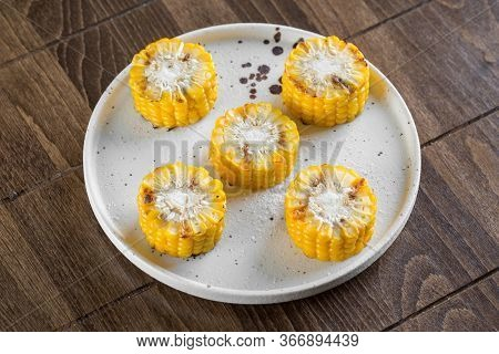 Grilled Corn Served On A White Plate.