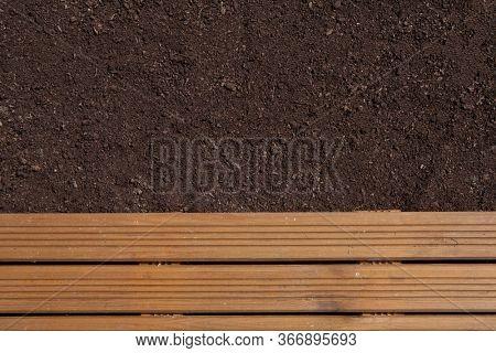 Brown garden soil and wooden path background. Gradening season concept