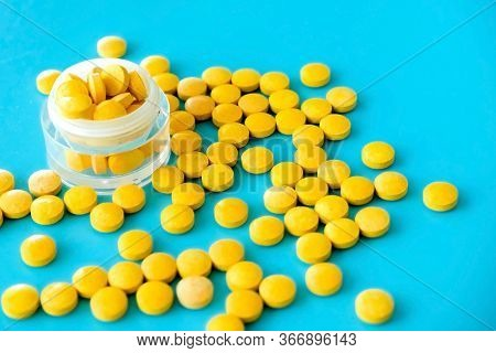 Yellow Bright Pills In A Jar And Crumbled On A Blue Background
