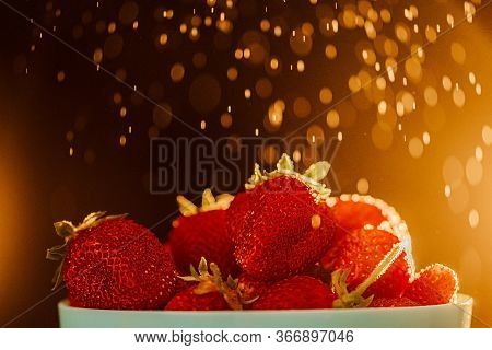 Red Juicy Ripe Strawberries In A Blue Vase On A Black Background. Drops Of Water, Warm Sunshine, Bac