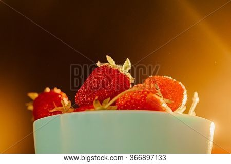 Red Juicy Ripe Strawberries In A Blue Vase On A Black Background. Sun Warm Rays, Back Light, Horizon