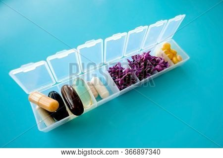 Capsules Lie In A Pill Box On A Blue Background. Box For Packing Tablets For A Week. Medicine And Fl