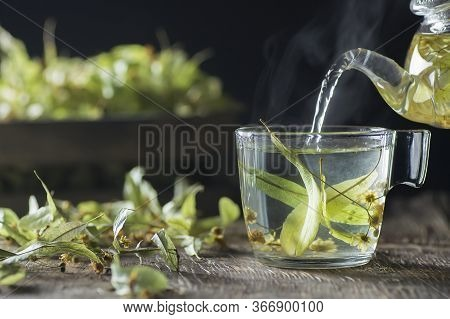 Glass Cup Of Linden Tea Or Blooming Tilia With Linden Blossom On Rustic Table. Hot Drink Winter Herb