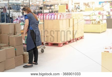 The Woman Employer Wear Surgical Mask And Uniform Stocks Shelves With Checking Inventories In Superm