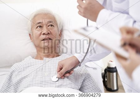 Asian Old Man Lying In Bed In Hospital Ward Being Examined By Doctor Using Stethoscope
