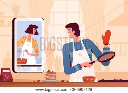 A Young Man Watches A Video Recipe On The Phone And Prepares Pancakes At Home In The Kitchen. The Co