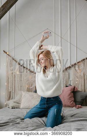 Happy young woman in headphones listening to music from smartphone and dancing on bed at home.