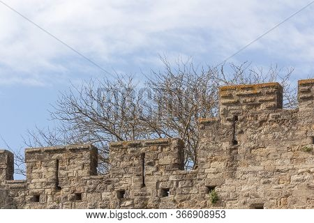 Battlement Fortress Wall With Loopholes Against The Sky