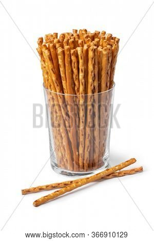 Glass with crunchy salted pretzel sticks isolated on white background