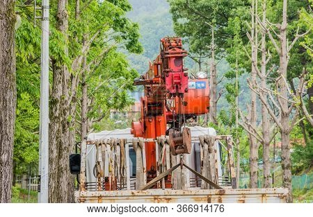Daejeon, South Korea; May 16, 2020: Rear View Of Construction Crane In Back Of Truck Parked On Tree