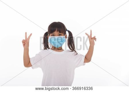 Little Asian Girl Wearing Mask Holding Hands Up With Two Fingers