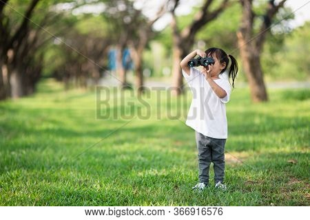 Happy Child Girl Playing With Binoculars. Explore And Adventure Concept