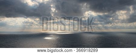 Bright Rays Of The Sun Through Dramatic Dark Clouds Over The Sea, Spots Of Light On The Water, Wide