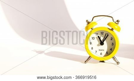 Yellow Alarm Clock With Large Shadow On White Background, Copy Space