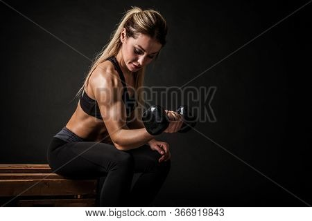 Fitness in gym, sport and healthy lifestyle concept. Beautiful athletic woman showing her trained body on dark background. Bodybuilder female model training biceps muscles with dumbbell.