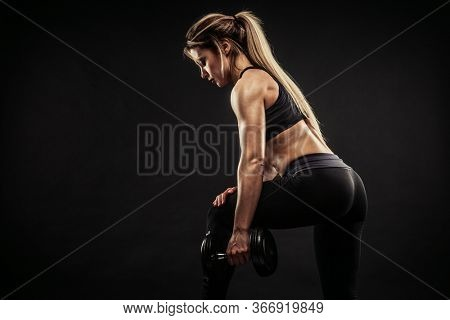 Fitness in gym, sport and healthy lifestyle concept. Beautiful athletic woman showing her trained body on dark background. Bodybuilder female model training triceps muscles with dumbbell.