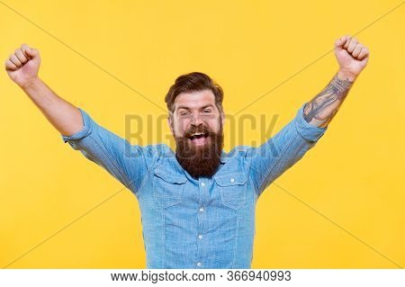 True Victory Not Easy To Achieve In Life. Happy Hipster With Raised Hands Yellow Background. Bearded