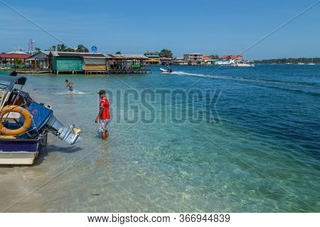 Bocas Del Toro, Panama: August 23, 2019: People at the colorful Caribbean buildings over the water with boats at the beach, Bocas del Toro, Panama