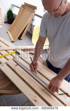 Handyman Checking Marks On Wooden Shelf With Construction Ruler. Grey-haired Man In T-shirt And Eyeg
