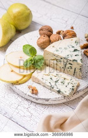 Segment Of Blue Mould Cheese - Gorgonzola With Pear And Walnuts On Wooden Board.  Top View Cheese -