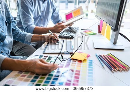 Young Colleagues Designers Working Together On A Creative Project And Color Samples For Selection, C