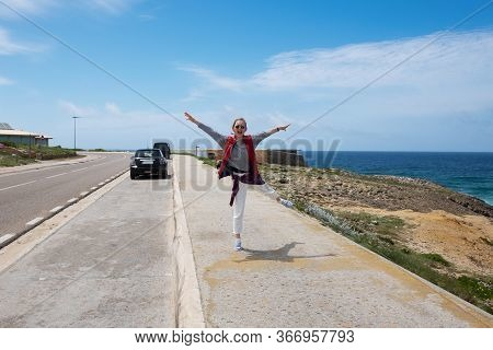 Happy Excited Young Woman Enjoying Walk Along Ocean Promenade, Posing And Shouting Of Joy. Front Vie