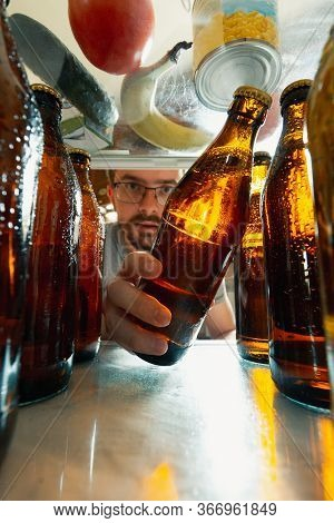 Caucasian Man Takes Cold Refreshing Beer From Out The Fridge, Inside View From Fridge Of Hand Holdin