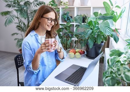 Enjoying Morning Coffee. Happy Business Woman, Young Female Freelancer In Glasses Sitting At Desk An