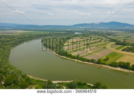 Establishing Aerial View Of Danube River. Green River Agricultural Field, Cloudy Sky In Summer.