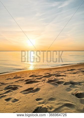Dawn On The Beach By The Sea. Quiet Calm Water With Small Waves. Reflection Of The Sun On The Water.