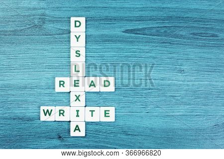 Dyslexia And Read Write Word Cubes On Blue Wooden Desk Background, Reading Difficulty Awareness And