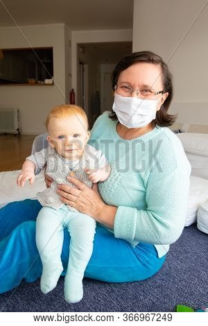 Cheerful Babysitter In Face Mask Playing With Baby In Home Interior, Sitting On Floor And Holding Ch