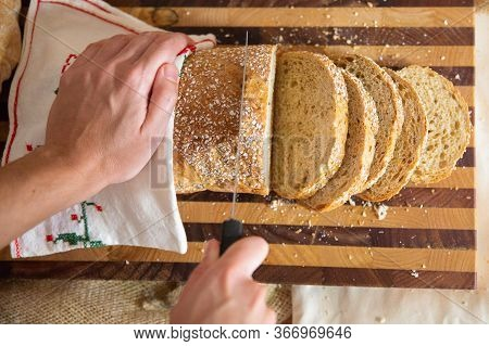 Baker Cutting Crusty French Loaf On Chopping Board. Closeup Shot, Top View. Traditional Food Or Baki
