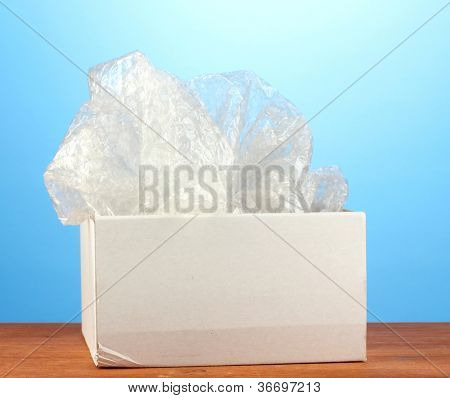 Opened parcel on blue background close-up