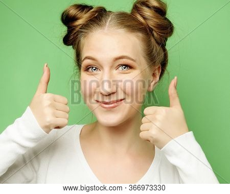 Happy young caucasian female making thumb up sign and smiling cheerfully