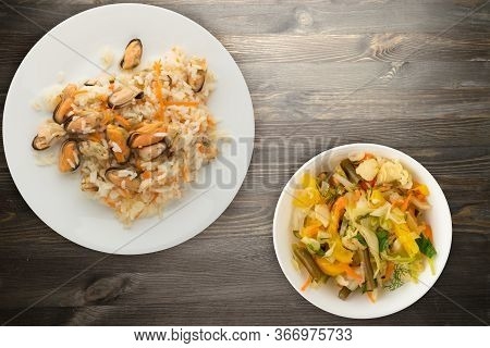 Rice With Mussels And Carrots On A White Plate. Rice With Mussels And Carrots On A Black Wooden Back