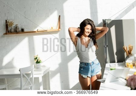 Attractive Girl Smiling While Using Laptop On Worktop In Kitchen